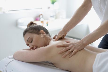Serene woman receiving massage on spa massage tableの写真素材 [FYI02320143]