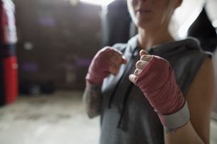 Female boxer with wrapped wrists in fighting stance in gymの写真素材 [FYI02320152]