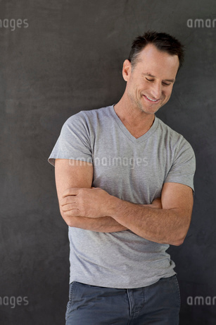 Portrait smiling, confident mature man in t-shirt against gray backgroundの写真素材 [FYI02320265]