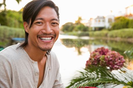 Portrait smiling, enthusiastic man at summer lakeの写真素材 [FYI02320326]