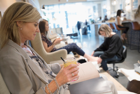 Woman reading book and drinking cocktail while getting pedicure in nail salonの写真素材 [FYI02320523]