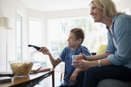 Mother and pre-adolescent son watching TV and eating popcorn in living roomの写真素材 [FYI02320534]