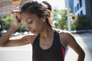 Close up tired female runner wiping sweat from forehead on urban streetの写真素材 [FYI02320584]