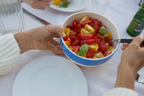 Personal perspective woman serving fresh, healthy tomato salad at tableの写真素材 [FYI02320592]