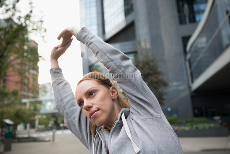 Female runner stretching arms on urban streetの写真素材 [FYI02320597]