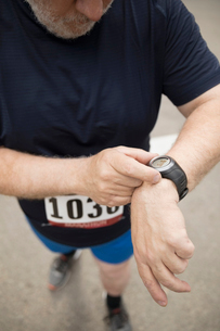 Close up male marathon runner checking smart watchの写真素材 [FYI02320598]