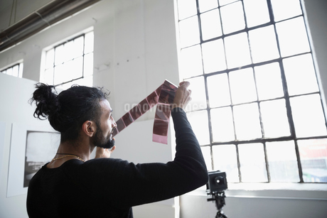 Male photographer examining photograph negatives in art studioの写真素材 [FYI02320634]