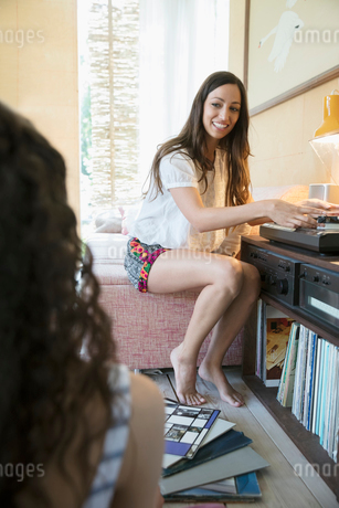 Female friends listening to music, playing vinyl records on record player in living roomの写真素材 [FYI02320638]