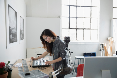 Female photographer reviewing photographic slides in art studioの写真素材 [FYI02320684]