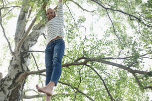 Portrait barefoot hipster man hanging from treeの写真素材 [FYI02320740]