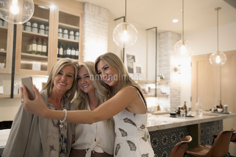 Blonde mother and adult daughters taking selfie in salonの写真素材 [FYI02320756]