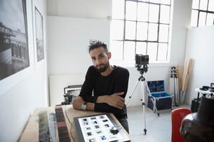 Portrait confident male photographer reviewing photographic slides in art studioの写真素材 [FYI02320818]