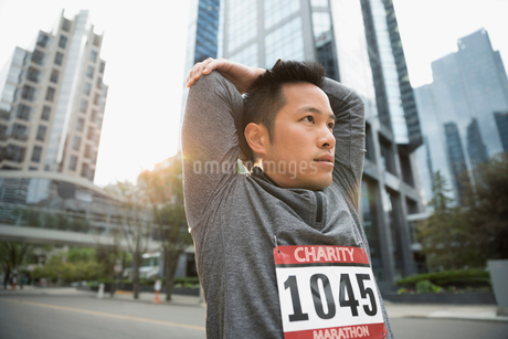 Male marathon runner stretching arms on urban streetの写真素材 [FYI02320867]