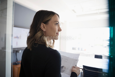 Businesswoman with paperwork looking away in conference roomの写真素材 [FYI02320868]