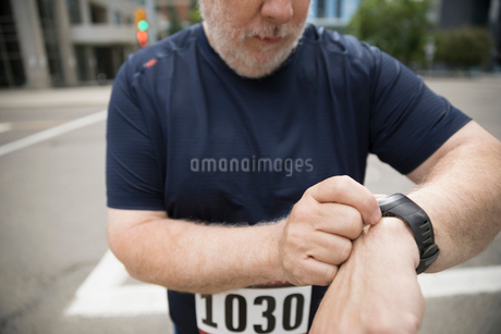 Close up male marathon runner checking smart watchの写真素材 [FYI02320907]