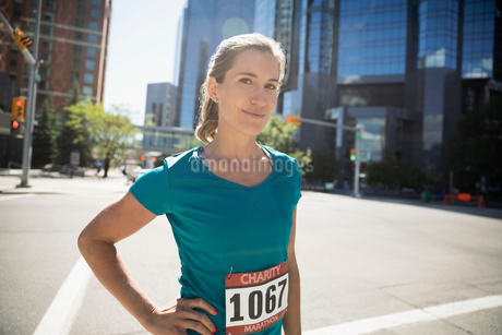 Portrait confident female marathon runner standing on sunny urban street cornerの写真素材 [FYI02320909]