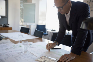 Male architect reviewing, editing blueprints in conference roomの写真素材 [FYI02320919]