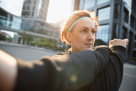 Female runner stretching arm on urban streetの写真素材 [FYI02320920]