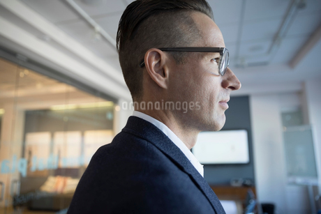 Pensive businessman looking away in conference roomの写真素材 [FYI02320923]