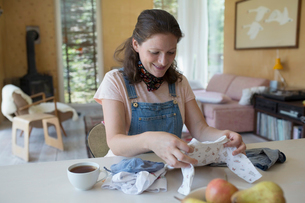 Pregnant woman folding baby clothes at dining tableの写真素材 [FYI02320932]