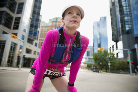 Tired female marathon runner resting with hands on knees on urban streetの写真素材 [FYI02320945]