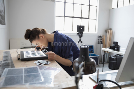 Female photographer reviewing photographic slides with lens magnifying loupe in art studioの写真素材 [FYI02320973]