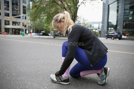 Female runner tying shoelace on urban streetの写真素材 [FYI02320974]