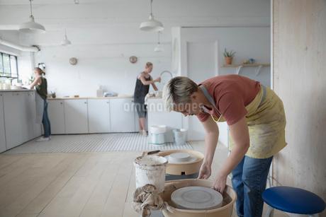 Female potter bending over pottery wheel in art studioの写真素材 [FYI02321028]