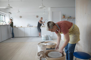 Female potter bending over pottery wheel in art studioの写真素材 [FYI02321028]