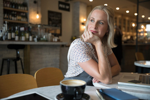 Smiling pensive woman using laptop, looking over shoulder in cafeの写真素材 [FYI02321032]