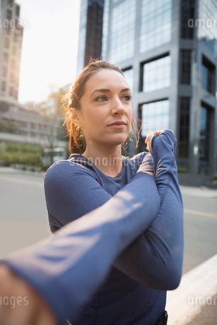 Young female runner stretching arm on urban streetの写真素材 [FYI02321057]