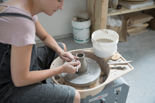 Female potter using tool to shape wet clay at pottery wheel in art studioの写真素材 [FYI02321059]