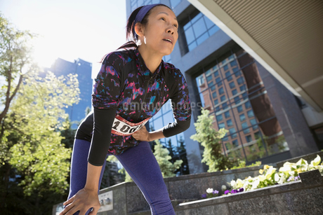 Tired mature female marathon runner resting with hands on knees below sunny urban highrise buildingの写真素材 [FYI02321102]