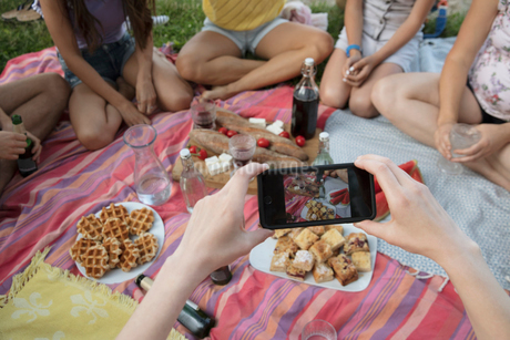 Personal perspective woman with camera phone photographing picnic foodの写真素材 [FYI02321133]