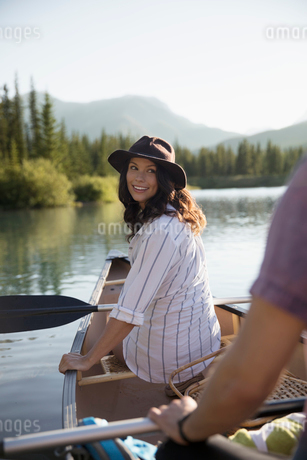 Smiling young woman in canoe on sunny summer lakeの写真素材 [FYI02321140]