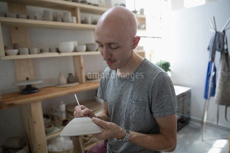 Close up male potter signing, marking bottom of handmade clay bowl in art studioの写真素材 [FYI02321142]
