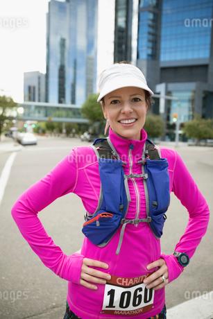 Portrait confident female marathon runner with water pack on urban streetの写真素材 [FYI02321206]