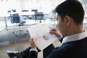 Businessman reviewing financial data and pie chart paperwork in officeの写真素材 [FYI02321207]