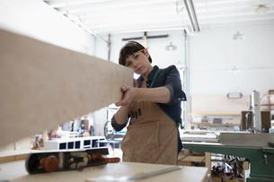 Focused female carpenter examining wood block in workshopの写真素材 [FYI02321222]