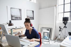 Female photographer with headphones working at laptop in art studioの写真素材 [FYI02321235]