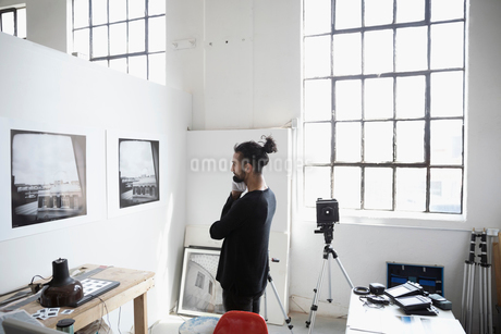 Focused male photographer examining large photography print hanging on wall in art studioの写真素材 [FYI02321238]