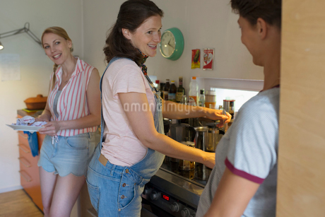 Pregnant woman and friends cooking in kitchenの写真素材 [FYI02321245]