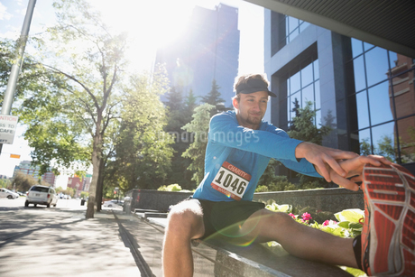 Young male runner stretching leg on sunny urban sidewalkの写真素材 [FYI02321277]