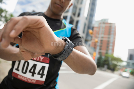 Male marathon runner checking smart watch on urban streetの写真素材 [FYI02321306]