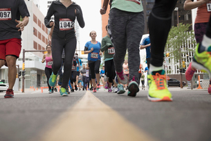 Surface level marathon runners running on urban streetの写真素材 [FYI02321313]