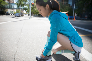 Young woman runner tying shoelace on sunny urban streetの写真素材 [FYI02321334]