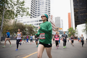 Focused female marathon runner in sunglasses running on urban streetの写真素材 [FYI02321335]