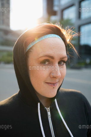 Close up portrait female runner with nose ring wearing hoodyの写真素材 [FYI02321367]