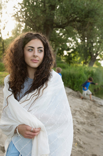Serene young woman wrapped in blanket on beachの写真素材 [FYI02321369]