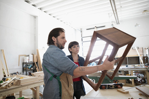 Serious carpenters examining wood table in workshopの写真素材 [FYI02321377]